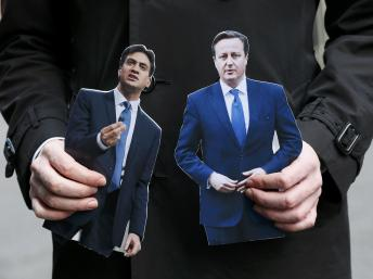 Um journalista com as fotos de Ed Miliband (esquerda) e David Cameron (direita). (REUTERS/Stefan Wermuth)