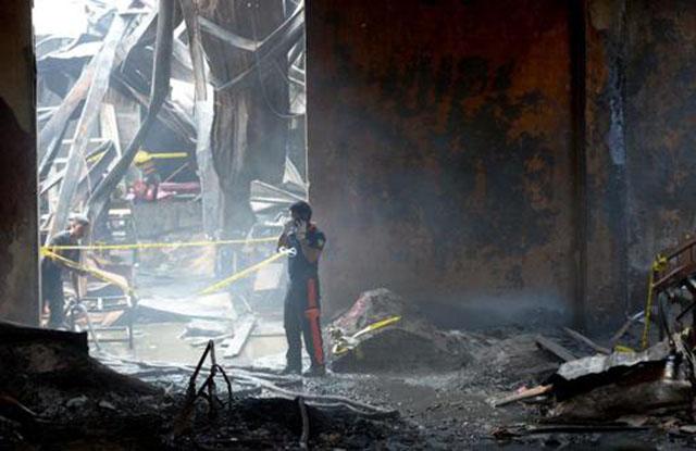 Bombeiros inspecionam fábrica de calçados após incêndio que matou 72 pessoas na área metropolitana de Manila (Foto: Ted Aljibe/AFP)
